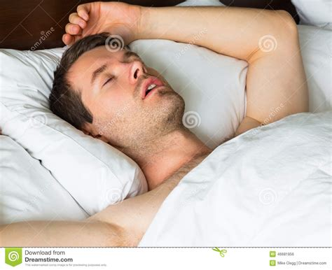 man sleeping in bed sleeping man in bed with his arm up