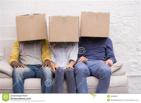 people sitting on a couch casual people sitting on couch with boxes over heads stock