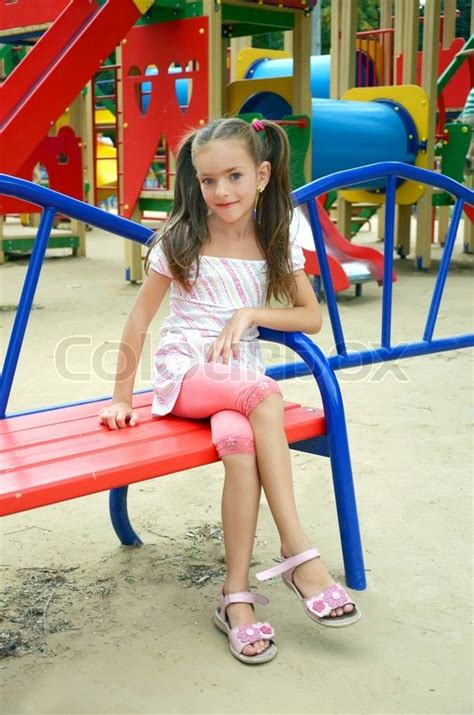 candid preteens girl sitting on a bench in child s park stock photo