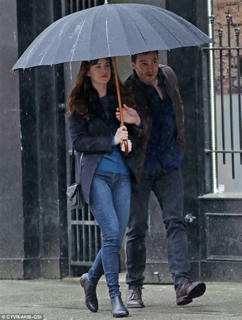 fifty shades darker filming now dakota johnson and jamie dornan huddle under an umbrella