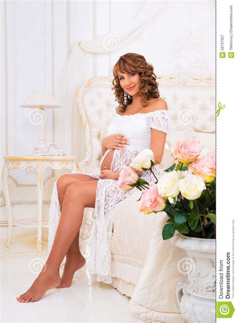 bed dress beautiful pregnant girl in a white lace dress sit on a bed