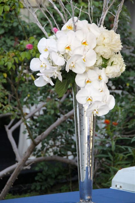 Silver Vase Orchids by A Arrangement In A Silver Conical Mercury Glass Vase