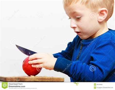 boy child kid preschooler with knife cutting fruit apple