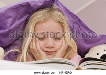 bett decke lies in bed reading book stock photo royalty free