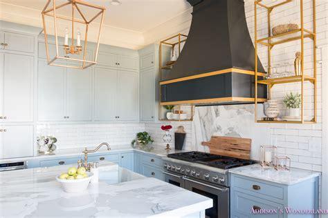 Kitchen white marble calcutta gold open shelves gold black vent hood blue gray cabinets shaker