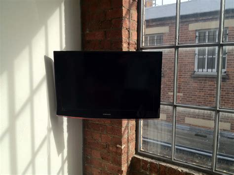 Corner Wall Mount TV Storage With Red Brick Wall Panels