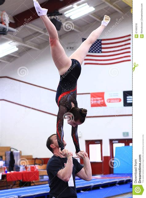 gym couch gymnastics coach and athlete doing acrobatics editorial