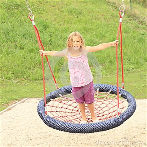 net swing little girl standing on a net swing stock photo image