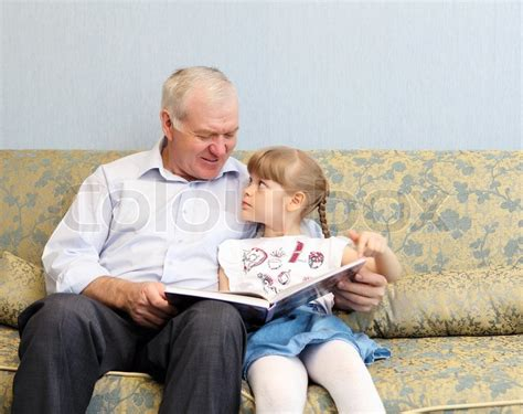 grandfather and granddaughter sitting on the sofa and