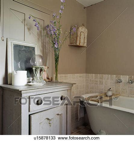 beige and gray bathroom stock photo of grey painted cupboard beside rolltop bath