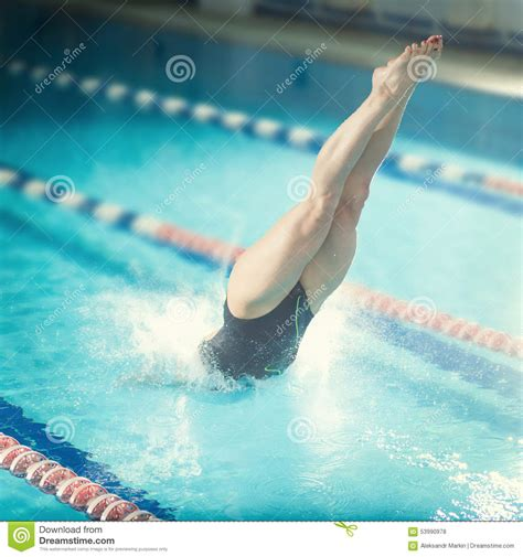 dive sport swimmer that jumping into indoor swimming stock
