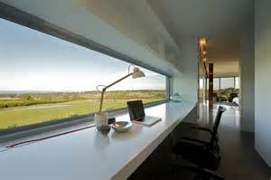 Modern home office workspace with long desk and panoramic views