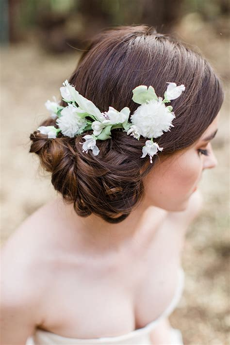white wedding hairstyles low updo wedding hairstyle with white elodie flower comb