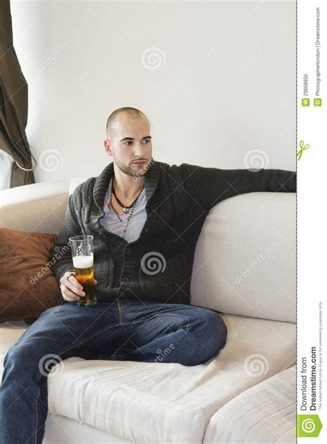sitting in sofa young man sitting comfortably on sofa holding a drink