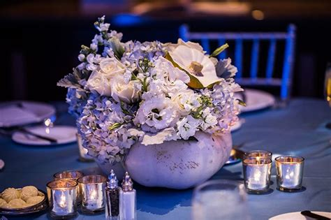 a pumpkin centerpiece adds a tale touch to a cinderella inspired wedding reception decor