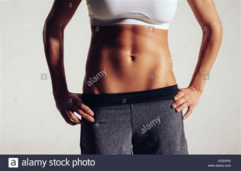 abs sections mid section of fit woman s torso with her hands on hips