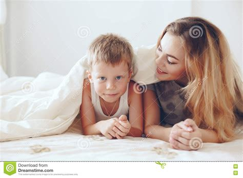 mother and son bedroom scene mother plays with son in bed stock photo image 70400799