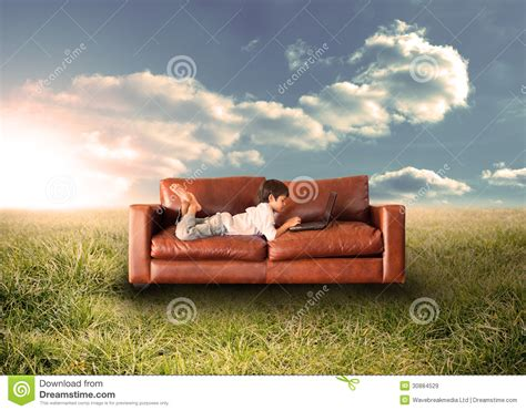 couch photography child using laptop on couch in field royalty free stock