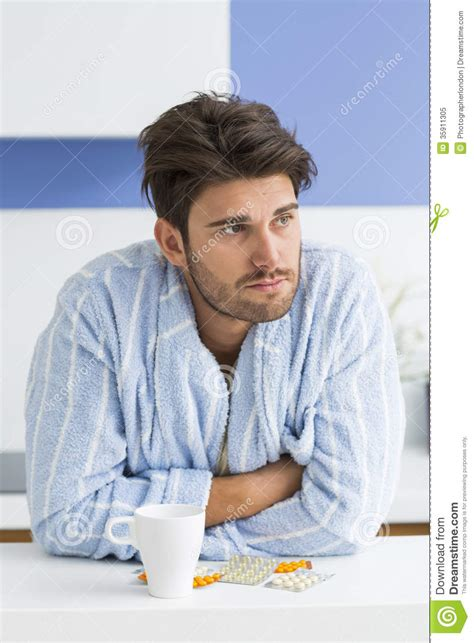 Top Kitchen Designers young ill man with coffee mug and medicine leaning on
