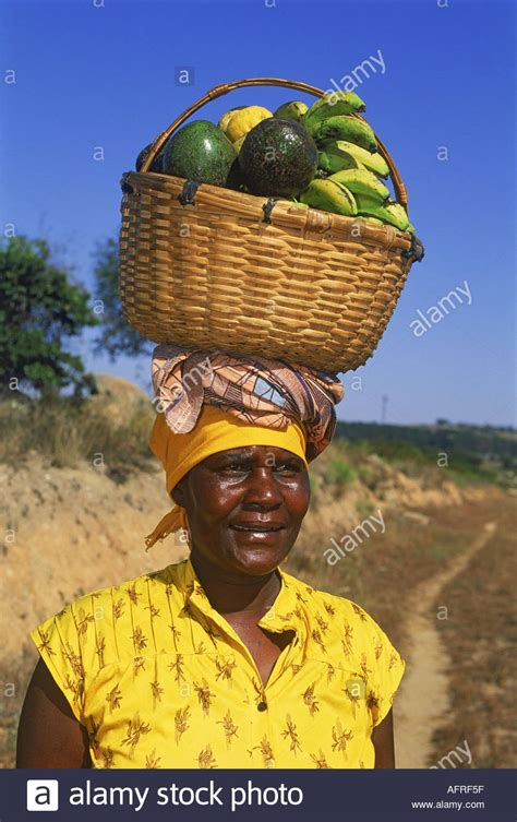woman with fruit basket on head black woman with basket of fruit balanced on head in