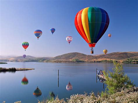 hot air balloons colourful mountains reflection water