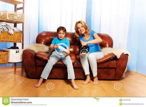 the last mama on the couch play mother and child playing with steering wheels stock photo