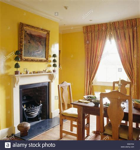 gilt room large gilt framed mirror above fireplace in yellow dining room with stock photo royalty free