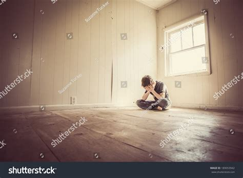 in my room alone sad boy alone in a bare room stock photo 189053942