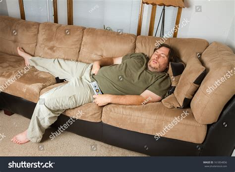 fat man on couch fat man sleeping on the couch with his hand down his pants