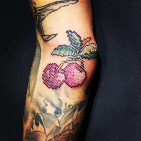 tattooed cross stitch man cross stitch cherry tattoo on the right elbow tattoo