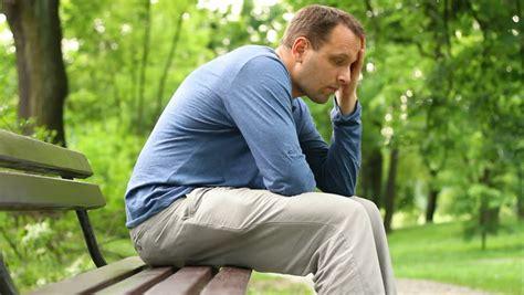 man sitting on bench sad young man portrait sitting on park bench camera