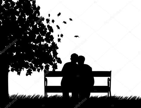 couple sitting on bench lovely retired elderly couple sitting on bench in park in autumn or fall stock