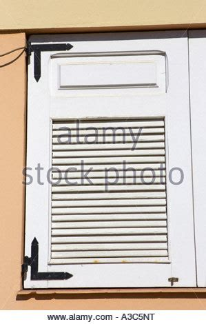 shutters on side of house white spanish colonial house window trimmed in light blue with stock photo royalty