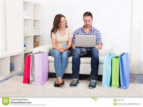 couch shopping online young couple sitting on couch shopping online stock photo