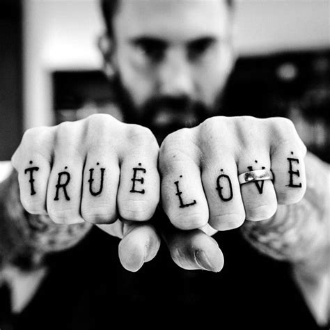 tattoo on each finger matching knuckle tattoo on adam levine each finger has