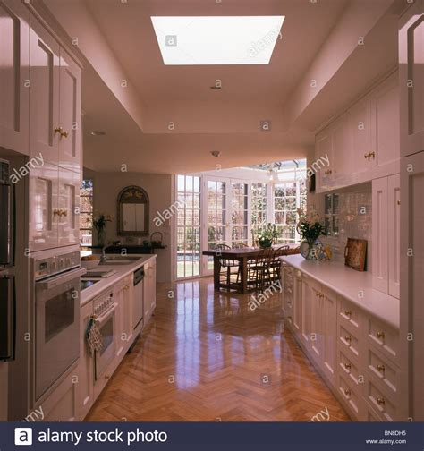 galley kitchen open to dining room wooden parquet flooring in large modern galley kitchen and