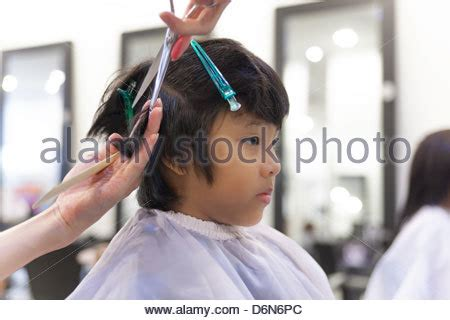 boys taken to beauty salon young boy getting his first haircut from a barber while