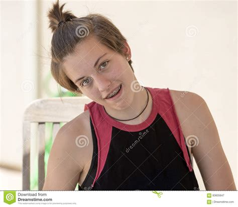 brace hair teenage girl with short hair sitting with her head tilted