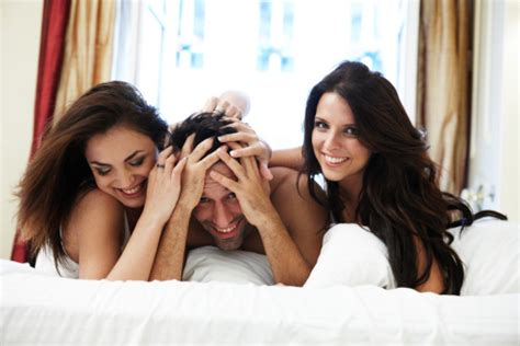 two women in bed young man with two women in luxurious bed stock photo