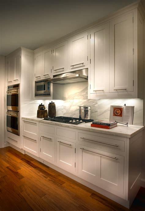 sleek kitchen cabinets calacatta backsplash is featured in this sleek kitchen with white cabinets and silver hardware