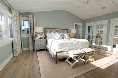 steely light blue bedroom walls wide plank rustic wood floors patterned curtains lots of