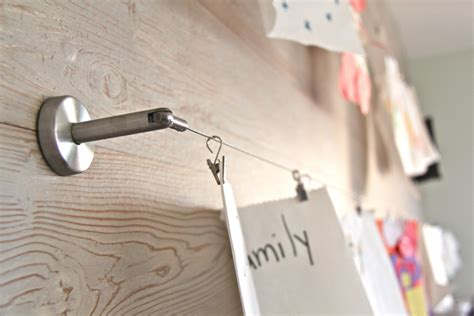 hang photos from wire using ikea s deka curtain wire and clip to hang children s