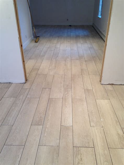 after remodel hallway house design with ceramic tile flooring that looks like wood planks and