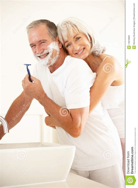 with wife in bathroom senior man shaving in bathroom mirror with wife stock