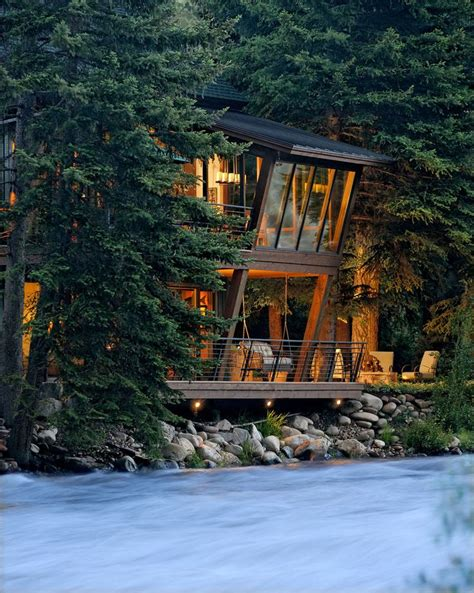 mountain cabin with angled windows a rushing river