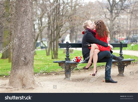 kissing bench happy romantic couple hugging and kissing on a bench stock