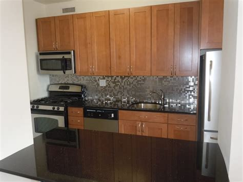 backsplash for black granite countertops kraftmaid walnut cabinets stainless backsplash black