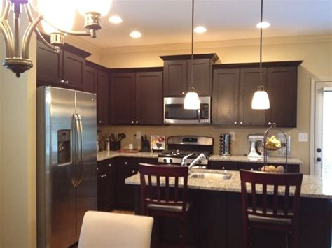 white granite with espresso cabinets and mini pendant light shades for small kitchen