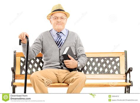man sitting on bench senior man sitting on a wooden bench with book stock