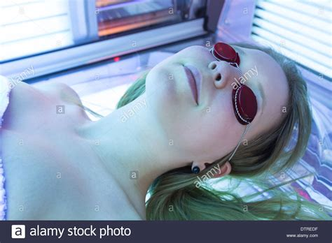 tanning bed nudes man with sunglasses on tanning bed in solarium stock photo